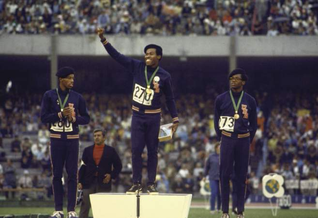 Lee Evans (c), Larry James (g) et Ronald Freeman (d) en béret noir sur le podium du 400 m aux JO de Mexico, en 1968.